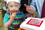 © Joel Goodman - 07973 332324 . 14/06/2016 . Burnley , UK . SHAUN CLOUGH (two) takes a lump from a VOTE REMAIN cake during a posed photo opportunity with Alison McGovern MP, Ed Balls and Yvette Cooper MP , campaigning for Remain , in the EU referendum , at Giant Leap Child Care and Learning House in Burnley . Photo credit : Joel Goodman