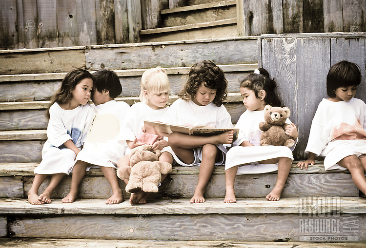 group of six multi-ethnic children reading on steps