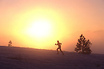 A photo of a silhouette of a woman running across the snow at sunrise.