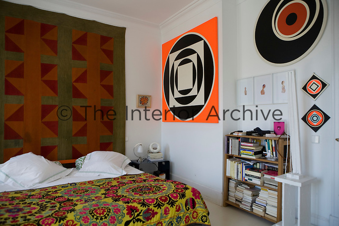 A modern bedroom with a brightly coloured patterned cover on the bed and pop-art paintings and a folk-art quilt hung on the walls