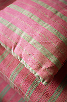 A detail of a pile of red and green striped cushions