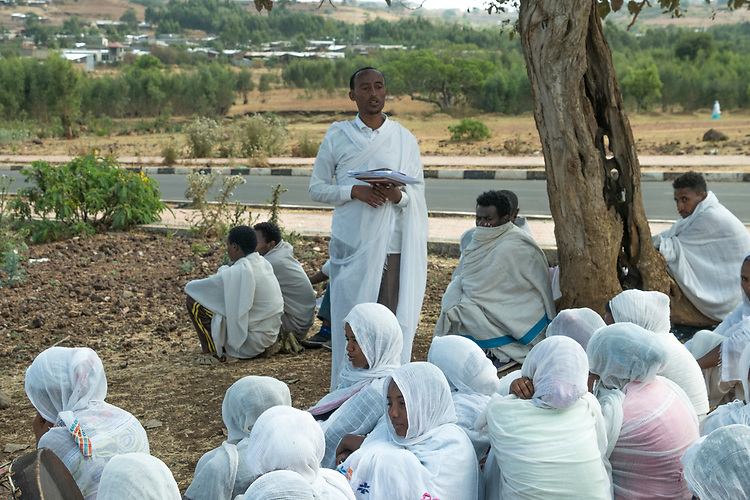 The daily lives of Ethiopian Orthodox people is displayed alongside roadways.  In this case a leader is reading scripture to his followers.