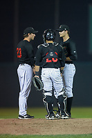Great Falls Voyagers pitching coach John Ely (23) has a meeting on the mound with relief pitcher Blake Battenfield (22) and catcher Carlos Perez (20) during the game against the Helena Brewers at Centene Stadium on August 18, 2017 in Helena, Montana.  The Voyagers defeated the Brewers 10-7.  (Brian Westerholt/Four Seam Images)