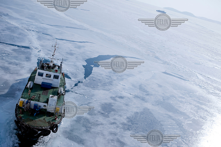 A navigation boat guids the Eastern Dream ferry into the port of Vladivostok, breaking through the ice-covered Sea of Japan.