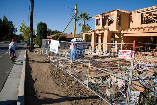 A cyclist passing by a large two-story conventional wood frame house under construction. Large amounts of wood and other raw materials are being used to build this new house on a lot where a small single-story home was demolished. Cupertino, California, USA