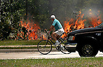 04/18/05.....Gary Wilcox/staff...... A cyclist rides past a brush fire off San Pablo Road in Jacksonville on Monday.(04/18/05).