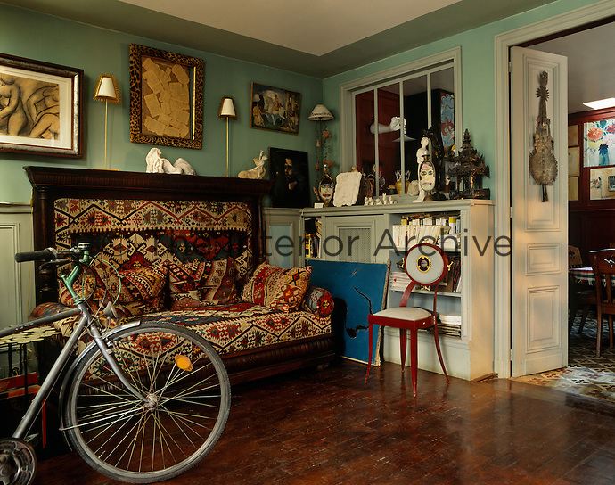 In the entrance hall a bicycle is propped against an old-fashioned kilim-covered settle covered with matching cushions