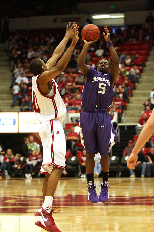 Justin Dentmon (#5), University of Washington senior guard, goes up for a shot over Washington State freshman, Marcus Capers (#0) during the Huskies game against the Cougars at Friel Court in Pullman, Washington, on January 3, 2009.  The Huskies prevailed in the game 68-48 to break a seven game losing streak to the Cougs.