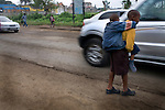 Mutava carrying Braise on his back as they cross the road together on the walk to school.<br />