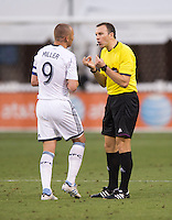Kenny Miller (9) of the Vancouver Whitecaps talks to referee Matthew Foerster during a Major League Soccer match at RFK Stadium in Washington, DC. D.C. United lost to the Vancouver Whitecaps, 1-0.