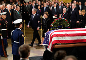 Former President George W. Bush, former first lady Laura Bush, walk past the flag draped casket of former President George H.W. Bush in the Capitol Rotunda, Monday, Dec. 3, 2018 in Washington. (AP Photo/Pablo Martinez Monsivais/Pool)