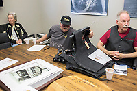 NWA Democrat-Gazette/CHARLIE KAIJO Judy Schreck of Bentonville and Gary Berger of Bentonville wait for the club meeting to begin as Ed Schreck of Bentonville (center) looks through a stack of vests at the Heritage Indian Motorcycle club and show room in Rogers, AR on Saturday, September 9, 2017. The Indian riders gathered to discuss plans for the upcoming Bikes, Blues and BBQ rally