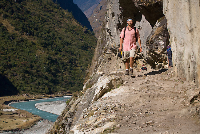 A TREKKER walks along a HIKING TRAIL hewn from a cliff face above the MARSYANDI RIVER on the ANNAPURNA CIRCUIT near Manang - NEPAL HIMALAYA (MR)