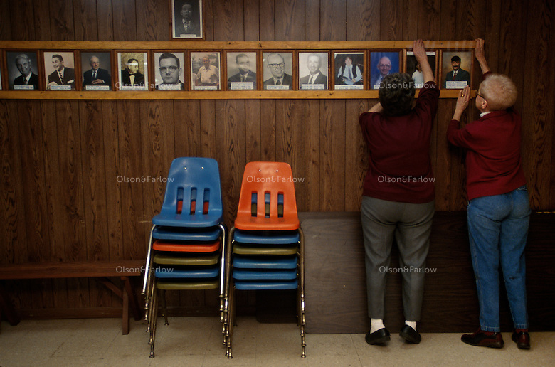 Preparing for a meeting, two women friends straighten photographs of public officials of their town in a wall of the community center.
