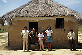 Roraima, Brazil. Family of Macuxi indians outside their adobe and thatch house.