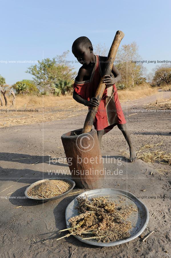 South Sudan Rumbek , Cuibet , Dinka boy prepares flour from Sorghum seeds with wooden mortar / SUEDSUDAN Rumbek , Cuibet County, Dinka Junge zerstampft Sorghum Koerner zu Mehl im Holzmoerser