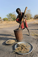 South Sudan Rumbek , Cuibet , Dinka boy prepares flour from Sorghum seeds with wooden mortar / SUEDSUDAN Rumbek , Cuibet County, Dinka Junge zerstampft Sorghum Koerner zu Mehl im Holzmoerser