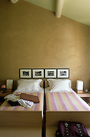 In a country bedroom bedcovers in a pink and yellow stripe contrast with the earthy tones of the plastered walls