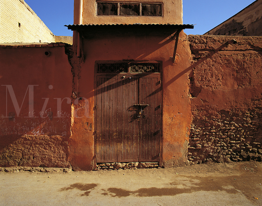 Locked and shuttered doorway in dark-red wall, Marrakesh, Morocc