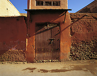 Locked and shuttered doorway in dark-red wall, Marrakesh, Morocc