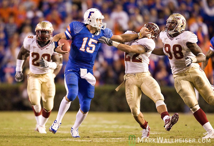 Gator quarterback Tim Tebow (15) holds off Korey Mangum (22) and the Seminole defense in the second half of the annual Florida vs Florida State NCAA football game in Gainesville, Florida November 28, 2009.  The Florida Gators defeated the Florida State Seminoles 37-10 for the 5th year in a row.