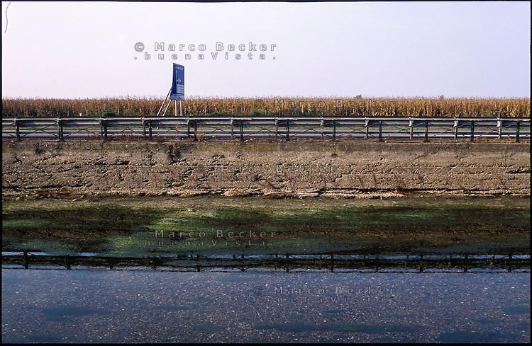 Vermezzo (Milano). Il Naviglio Grande in secca e la strada provinciale, un cartello stradale e i campi --- Vermezzo (Milan). Shallow water in the canal Naviglio Grande and the county road, a road sign and the fields