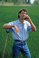 young farmer using cellular flip phone in rice field. farmer. California.