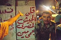 EGITTO, IL CAIRO 9/10 settembre 2011: assalto all'ambasciata israeliana. Migliaia di manifestanti egiziani, ancora infuriati per l'uccisione di cinque guardie di frontiera egiziane da parte dell'esercito israeliano, hanno fatto irruzione nella sede diplomatica israeliana e sono stati poi sgomberati da esercito e polizia egiziana. Nell'immagine: il braccio di un manifestante sotto lo sguardo di un poliziotto egiziano.<br /> Egypt attack to the Israeli embassy  Attaque &agrave; l'ambassade israelienne Caire