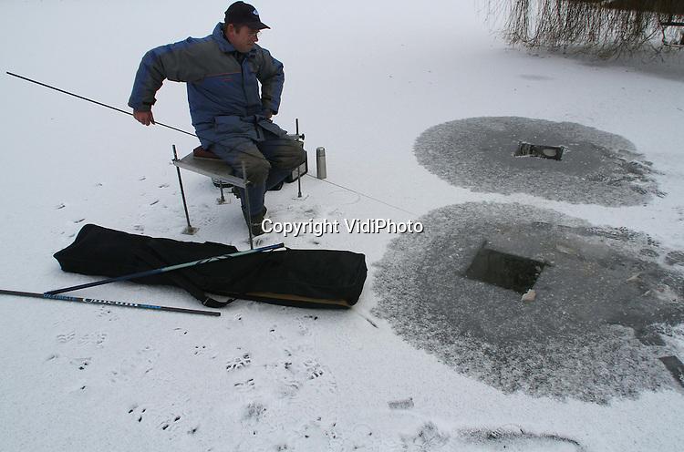 """Foto: VidiPhoto..NIJKERK - Een eenzame sportvisser op Plas Watergoor in Nijkerk probeert vrijdag zijn geluk bij een wak in de ondergesneeuwde ijsvloer. Het ijs is net dik genoeg om de man en zijn hengels te dragen. De viswedstrijd van zaterdag is door hengelsportvereniging """"Hoop op Geluk"""" in Nijkerk vanwege de ijsvorming afgelast, maar deze visser laat zich daardoor niet weerhouden. Wakvissen is dankzij enkele jaren flinke vorst achter elkaar in Nederland weer populair aan het worden. In Scandinavië en Oost-Europa wordt deze vorm van visserij vaak beoefend."""