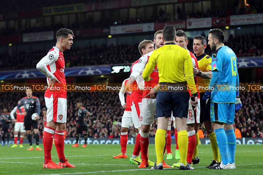Referee, Tasos Sidiropoulos, urges Arsenal's Laurent Koscielny, to leave the field after being sent off, but the Arsenal captain continues to speak to the referee's assistant near the goal who seemed to influence the referee's decision during Arsenal vs FC Bayern Munich, UEFA Champions League Football at the Emirates Stadium on 7th March 2017
