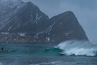 Surfer in stormy winter conditions at Unstad beach, Vestvågøy, Lofoten Islands, Norway