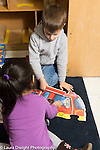 Education Preschool 3-4 year olds boy and girl working on floor puzzle together