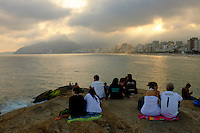 People watch a general view of Ipanema beach at sunset