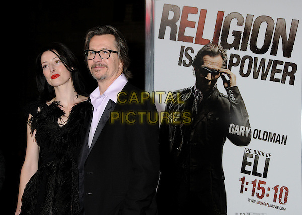 "ALEX EDENBOROUGH & GARY OLDMAN.at Alcon Entertainment's L.A. Premiere of ""The Book of Eli"" held at The Chinese Theatre in Hollywood, California, USA, .January 11th 2010. .half length couple black dress feather feathers suit jacket glasses pink purple shirt goatee facial hair .CAP/ADM/BP.©Byron Purvis/AdMedia/Capital Pictures."