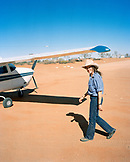 AUSTRALIA, Outback, portrait of a young female pilot walking towards plane. She is one of the youngest bush pilot.