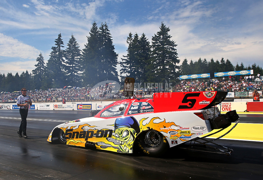 Aug. 1, 2014; Kent, WA, USA; A crew member guides NHRA funny car driver Cruz Pedregon back after his burnout during qualifying for the Northwest Nationals at Pacific Raceways. Mandatory Credit: Mark J. Rebilas-