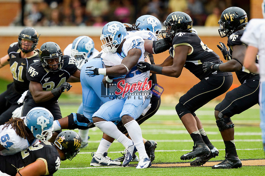A.J. Blue (15) of the North Carolina Tar Heels is wrapped up by Desmond Floyd (94) at BB&T Field on September 8, 2012 in Winston-Salem, North Carolina.  The Demon Deacons defeated the Tar Heels 28-27.  (Brian Westerholt/Sports On Film)
