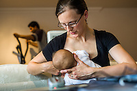 A mother doing home working at her computer while breastfeeding her baby and helping her to latch on properly. Her husband in the background is using his excercise machine after coming home from his job.<br /> <br /> 15/05/2012<br /> Hampshire, England, UK