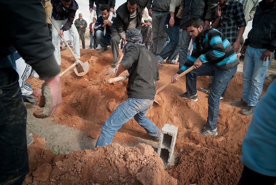 Earth is shoveled onto the grave at a funeral in Benghazi, Libya.