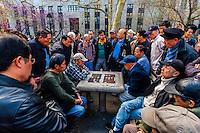 Older Chinese men playing Chinese chess, Columbus Park, Mulberry Street, Chinatown, New York City, New York USA.