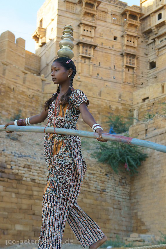 Aarti, an acrobat girl of a travelling acrobat family shows here art in the inner court of Jaisalmer Fort main gates, Rajastan, India.