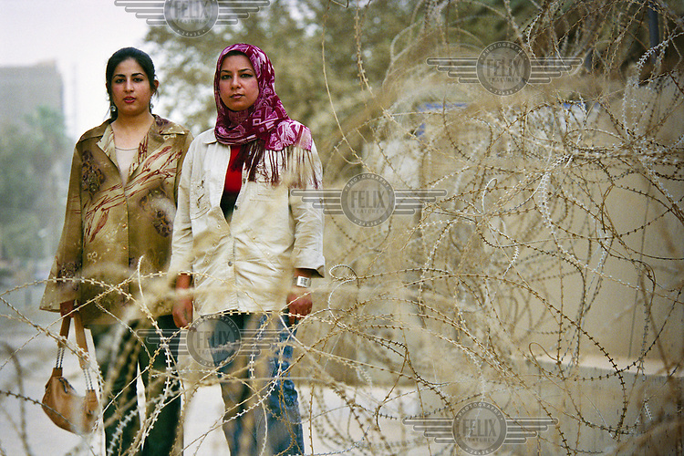 Rawa (left) and Hala Youssuf behind the barbed wire which is ubiquitous in Baghdad.