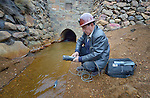 Freddy Llanos, a professor of mining engineering at Tomas Frias University, samples water quality downstream from the Kumurana Mine near Caiza D, Bolivia. The mine, which is closed, produces highly toxic acid runoff that negatively impacts the farms and lives of people living downstream. Llanos is working with an international coalition that is working with local miners and farmers to clean up the mine's runoff.