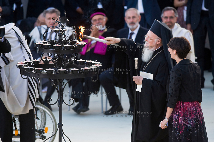 Assisi,Italy, September 20, 2016. Il Patriarca Bartholomew I  accende una candela al termine delle celebrazioni della giornata di preghiera per la Pace ad Assisi. Bartholomew I lights a candle during the closing event of an inter-religious prayer gathering, in front of the Basilica of St. Francis, Assisi, Italy. War refugees and leaders and representatives of several religions, including Christians, Jews, Muslims, Hindus and others, joined Pope Francis in a day of prayer for peace in Assisi, the hometown of St. Francis, who preached tolerance and gentleness.