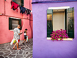 Pink and lavender walls, texting with shopping bags. The colorful village of Burano, Italy.