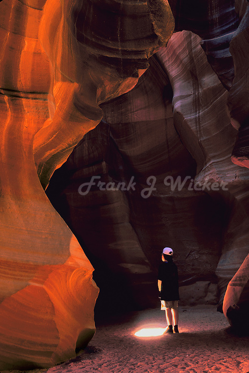 Navajo youngster (boy) standing in  the beam of light in the cavern of the Upper Antelope Canyon in the Navajo Tribal Park near Lake Powell and Page Arizona on the Colorado Plateau