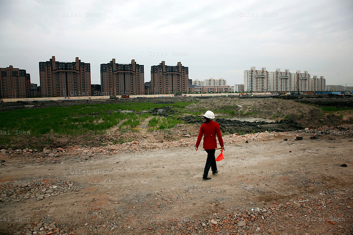 A woman walks through a construction site for residential developments in Shanghai, China on 13 May 2010. Investment in government infrastructure and real estate spending have surpassed foreign trade as the biggest contributor to China's growth, fueling fears of an economic slow down triggered by the debt burden.
