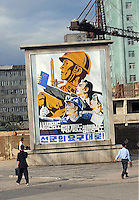 "People pass a propaganda poster in Pyongyang. The DPRK (Democratic People's Republic of Korea) is the last great dictatorship where the people are bombarded with images of the ""Eternal President"" Kim Il-sung who died in 1994  and his son and current leader Kim Jong-il who are worshipped like a God."