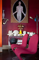 "In the small salon, furnished with a pair of Verner Panton chairs, a collection of Fulham Pottery created for the florist Constance Spry is displayed beneath a canvas ""Rebis"" by Matthew Stradling"