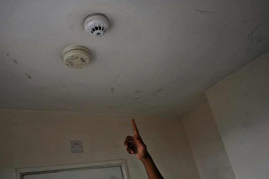 Tina Ngondo points to the fire alarm in her bedroom on the seventh floor of the Alexandra Court Temporary Hostel in Stoke Newington. Fire alarms are often triggered off in the middle of the night for hours due to poor levels of response and maintenance in the block.